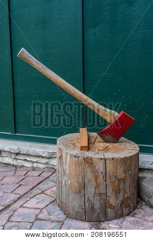 Red Axe and Kindling Sit on Log on front patio