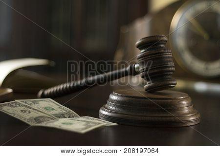 Judges gavel and Dolars on desk in courtroom.