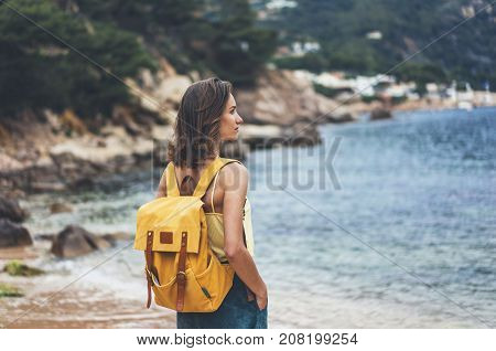 Back view hipster girl with backpack in sand coastline on nature landscape mock up. Traveler on background beach seascape and horizon mountain. Tourist look on blue sun ocean summer relax lifestyle