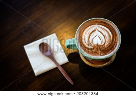 Homemade hot fresh cocoa with patterned white milk froth on surface in cup with wooden saucer (bottom plate) spoon and tissue serve on wooden table for beverage background - healthy diet concept.