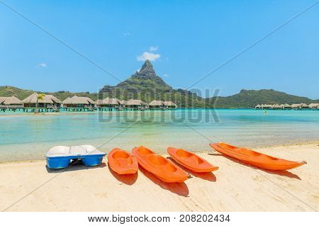 Orange kayaks on white sand beach Bora Bora Tahiti French Polynesia South Pacific. Concept for relaxation vacation resort