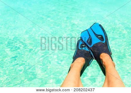 Female feet with blue snorkeler fins over turquoise blue water