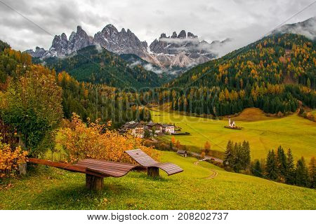 Amazing autumn view of Santa Maddalena village with wooden sunbed on foreground and Odle Mountain Peaks on background. Val Di Funes South Tyrol Dolomite Alps Italy.