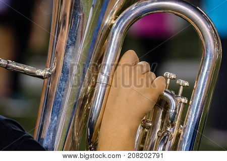 the right hand of a baritone player at rehearsal