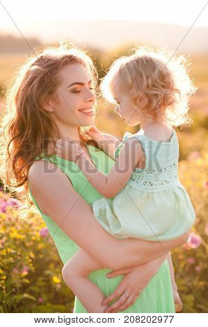 Happy mother holding baby girl 3-4 year old wearing similar dresses outdoors. Looking at each other. Motherhood. Summer time. 20s.
