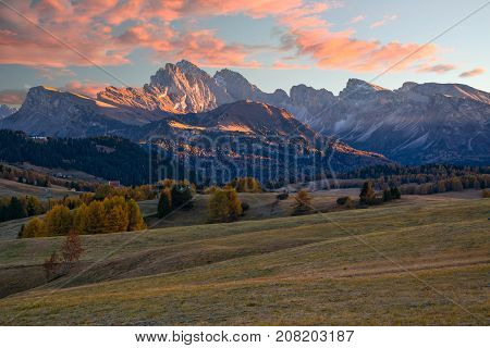 Amazing view of Alpe di Siusi - Seiser Alm - at sunrise. Majestic mountains in sunlit and colorful sky in background Dolomite Alps Italy