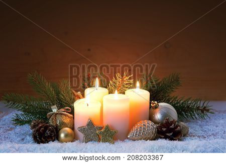 Christmas background with four white advent candles and golden decoration.