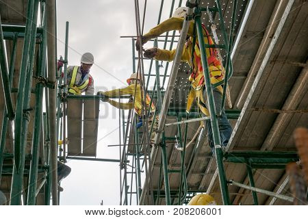 construction worker on scaffolding in industrial construction during sunset sky background over time job