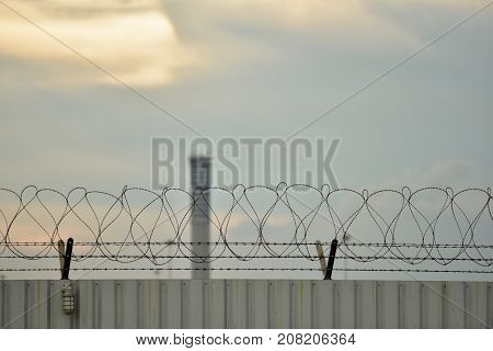 Barbed wire fence of the prison against sunset sky
