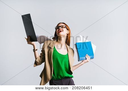 girl secretary with glasses laughs holding folders and files