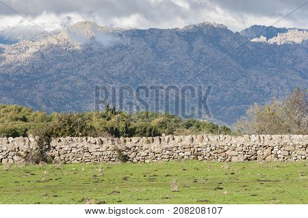 Stone wall in the field. In the background can be seen La Pedriza in Guadarrama Mountains. Photo taken from Dehesa de Navalvillar Colmenar Viejo Madrid Spain