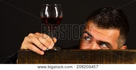 Man With Beard Holds Glass Of Wine On Brown Background