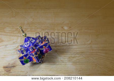 Blue enameled decorative star shaped Hanukkah dreidel on a wood table