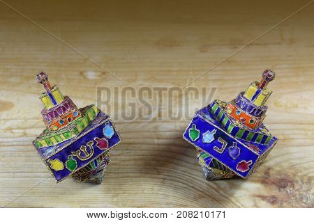 Two multicolored Hanukkah dreidels on a wood tabletop with space for text