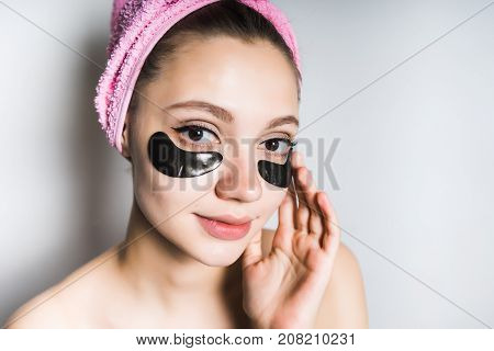 girl with a towel on her head puts on her face a black mask