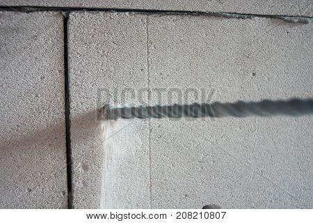 Big drill bit in hole of concrete closeup