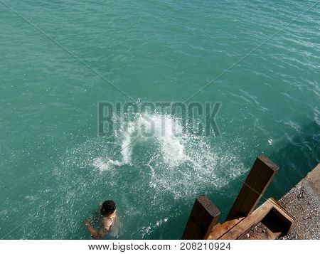 Latino young man swimming on a greenish ocean with some water splashing near a wooden ladder and cement platform.