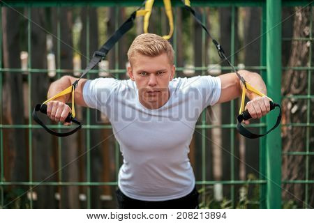 Man is an athlete, trains nature the city, summer training loops training, Balance motivation, tanned skin in shorts. Exercise the arms. Push-up on loops, training of pectoral muscles and back.