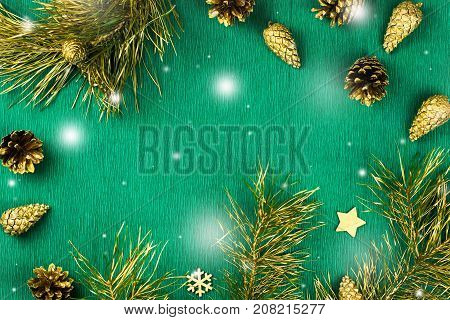 Christmas frame with fir tree branches, pine cones and golden ornaments on warm green background with snow falling, copy space. Christmas composition