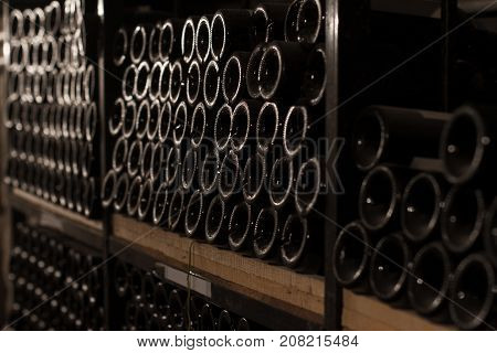 perspective view of rows of vintage red wine bottles on the shelves of a vinery wine cellar