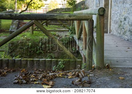 Photo of a wood railing with dry leaves and cold colours