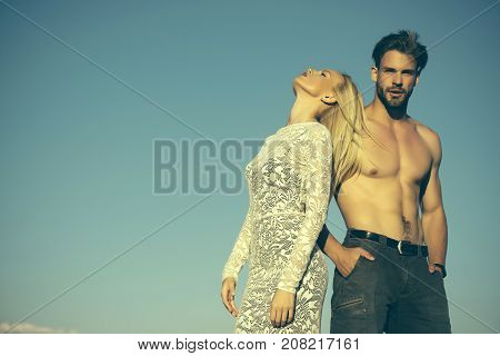 Woman or girl with long blond hair in lace dress. Man or macho with naked torso in jeans. Couple in love on blue sky. Fashion and beauty. Relationship heterosexual and lifestyle concept copy space