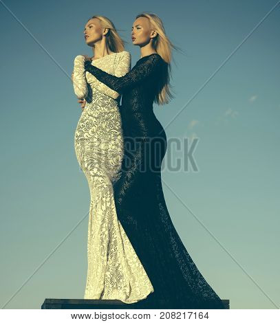 Two Girls With Long Blond Hair Posing On Blue Sky