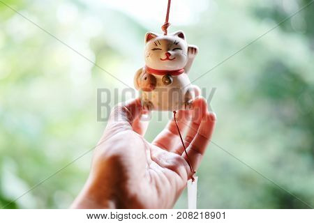 Woman hand is holding a Japan lucky cat doll is hanging on the window