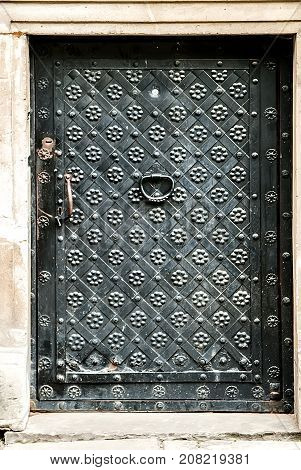 Vintage metal dark grey door decorated with forged flowers and grill.