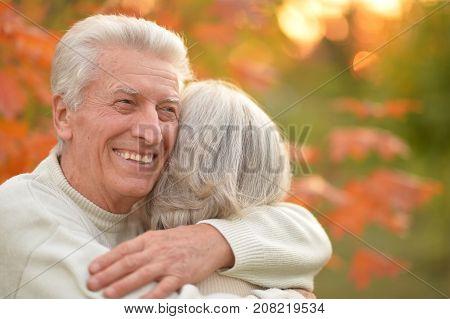 portrait of beautiful caucasian senior couple hugging   in the park