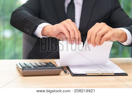 Hands of businessman ripping loan agreement at the desk break the rules - failure business concept