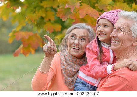Portrait of grandmother and granddaughter outdoors.  grandmother pointing with finger