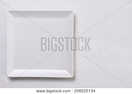 Flat Lay Above White Square Plate On The White Marble Background Table