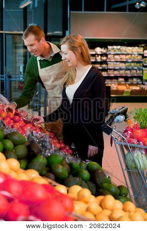 A woman buying groceries in a supermarket receiving help from a shop assistant
