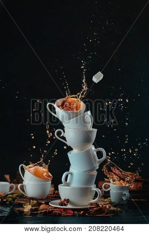 Stack Of White Coffee Cups With Dynamic Splashes And Coffee Drops On A Dark Background. Kitchen Mess