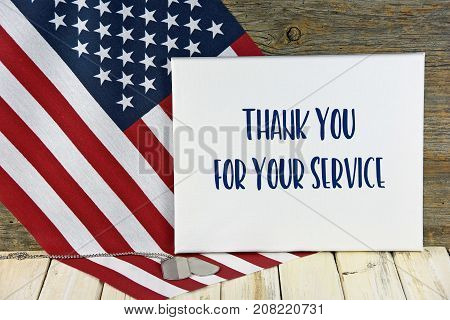 military dog tags and American flag on rustic wood with thank you sign for Veterans Day