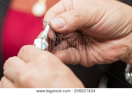 Close Up Of A Make Up Artist Hands Applying Cosmetic Glue On Fake Eyelashes