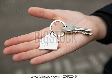 a female hand holds the keys to the apartment