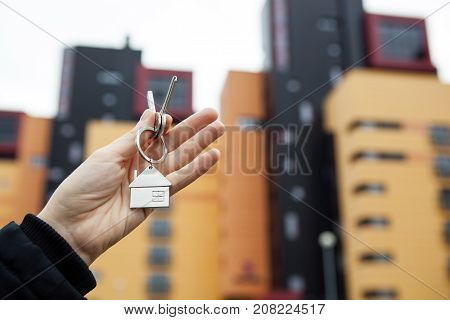 A woman's hand holds the keys on the background of new buildings