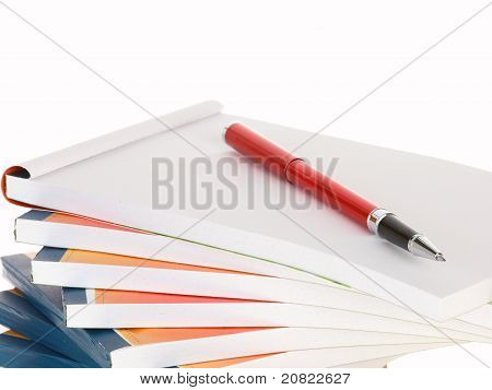 Red Pen On Notebook Stack