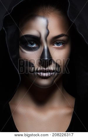 Halloween Portrait Of Young Beautiful Girl In A Black Hood. Skeleton Makeup Half Face