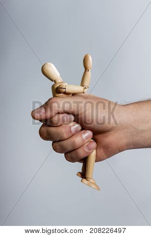 Male Hand Gripping A Stick Figure Of A Wooden Man. Stick Person Folded.