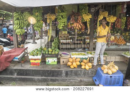 Galle Sri Lanka - April 11 2017: Market seller standing at a stall with different types of bananas and fruits