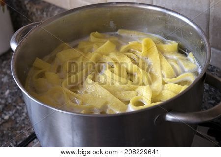 preparing handmade egg tagliatelle in metallic pot
