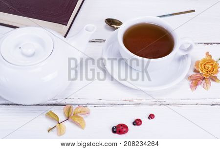 black tea in a round white cup with a saucer next to a white tea pot and a closed book