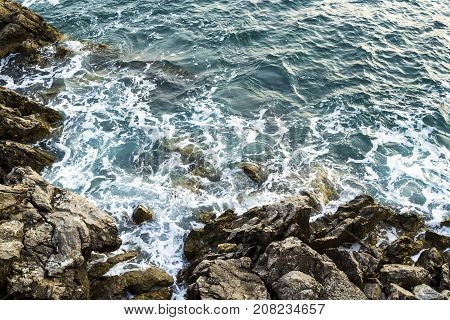 Huge stones in the sea and waves. Evening. View from above. Montenegro. The Budva Riviera