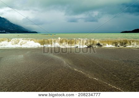 Sea wave in stormy weather. The turbid wave. Low clouds over the coast. Montenegrin beach in rainy weather. The sea and mountains of Montenegro. Budva. Becici