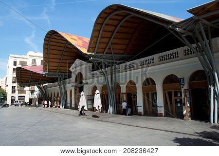 BARCELONA, SPAIN - AUG 30th, 2017: Front side of the public market Mercat de Santa Caterina. Guests have lunch in the Tapas bar. The market has a nice colorful curved roof.