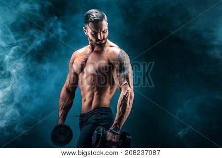 Young ripped man bodybuilder with perfect abs, shoulders, biceps, triceps and chest posing with a dumbbell, smoke studio shoot