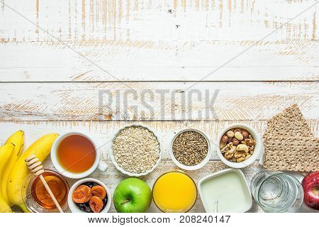 Healthy Food Fiber Source Breakfast Oatmeal Honey Fruits Apples Banana Orange Juice Water Green Tea Nuts. White Plank Wood Table. Rustic. Horizontal Border Composition.Flat Lay Top View.